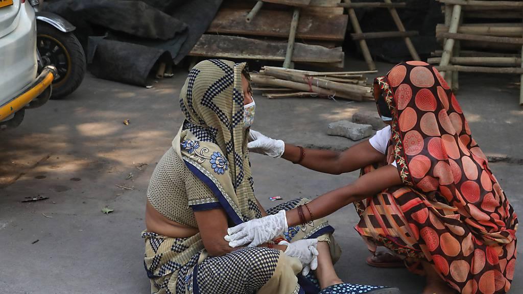 Die Angehörige eines Covid-19-Opfers wird während der Einäscherung des Leichnams im Krematorium Nigambodh Ghat in Neu-Delhi getröstet. Foto: Naveen Sharma/SOPA Images via ZUMA Wire/dpa