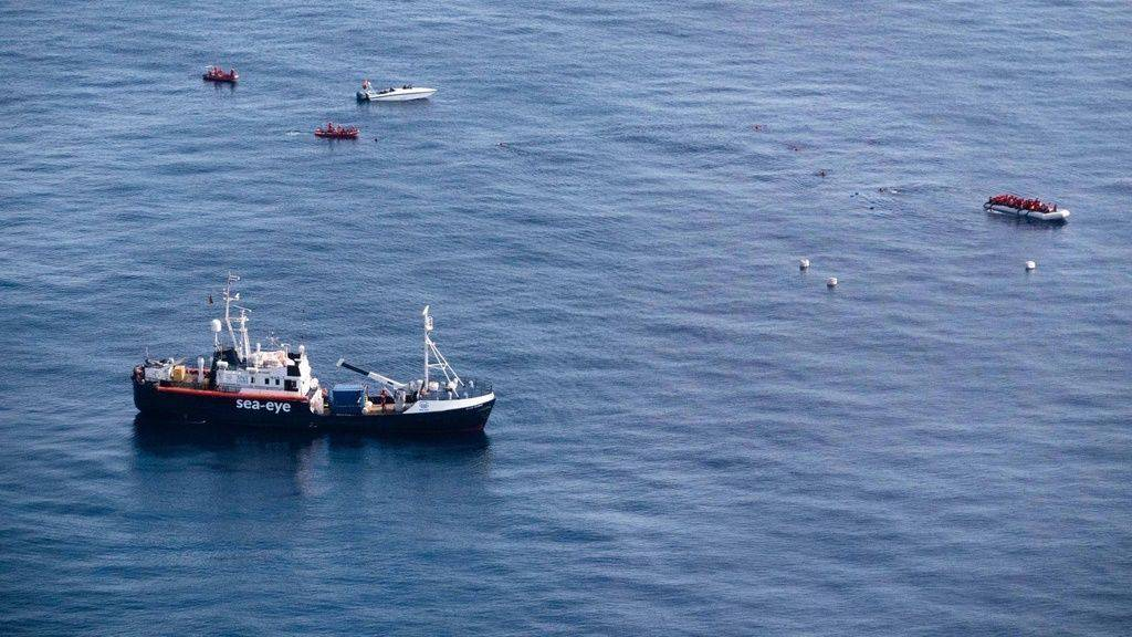 Auf dem von Sea-Eye veröffentlichten Bild vom Samstag ist die Alan Kurdi zu sehen, die sich vor der libyschen Küste einem Schlauchboot mit Flüchtlingen (oben rechts) nähert, während ein angeblich libysches Schnellboot (links oben) die Schiffe umkreist.