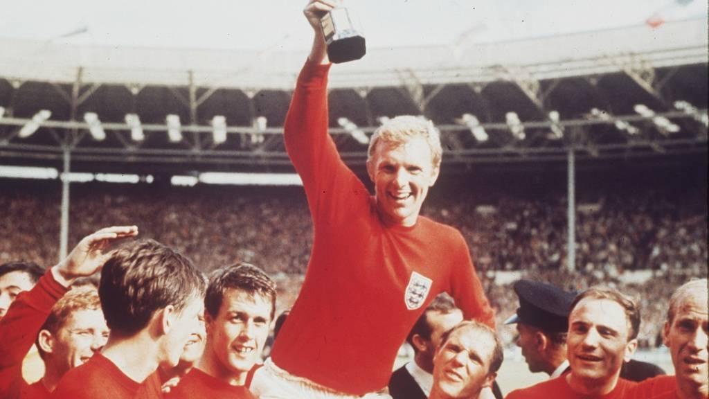 Die britische Fussballmannschaft bejubelt 1966 ihren Weltmeistertitel. Nachdem kürzlich bekannt wurde, dass Bobby Charlton (r) als fünftes Mitglied der damaligen Mannschaft an Demenz erkrankt ist, hat der britische Fussballverband Regeln zur Minimierung von Kopfbällen erlassen (Archivbild).
