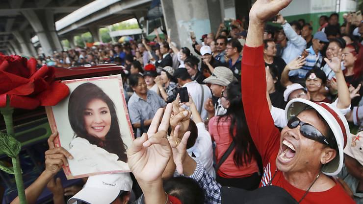 Unterstützer der früheren thailändischen Regierungschefin Yingluck Shinawatra halten bei einer Kundgebung in Bangkok ein Bild von ihr hoch. Yingluck soll nach Dubai geflohen sein. (Archiv)