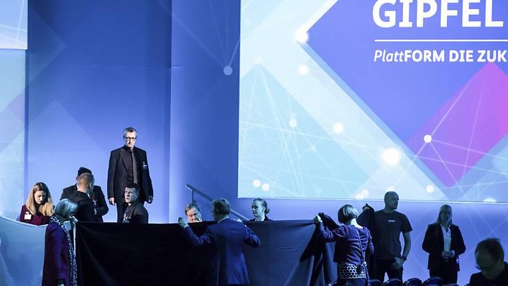 Deutschlands Wirtschaftsminister Peter Altmaier ist beim Digitalgipfel in Dortmund beim Gang von der Bühne gestürzt - nach dem Unfall schirmen Helfer ihn mit schwarzen Laken ab.