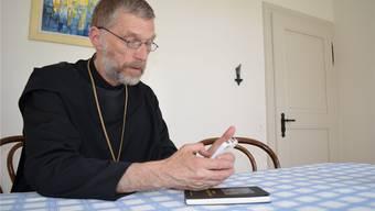 Abt Peter von Sury in einem Sprechzimmer im Kloster Mariastein: mit seinem iPhone und dem Regel-Buch von Benedikt.