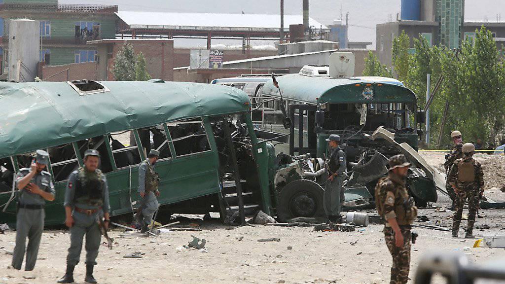 Die beim Anschlag stark beschädigten Fahrzeuge, umstellt von Sicherheitskräften