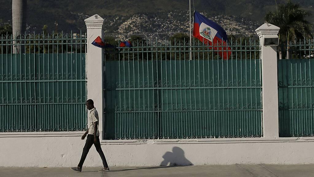 dpatopbilder - Die haitianische Flagge weht auf Halbmast vor dem Präsidentenpalast in Port-au-Prince, drei Tage nachdem Präsident Jovenel Moise in seinem Haus ermordet wurde. Foto: Fernando Llano/AP/dpa