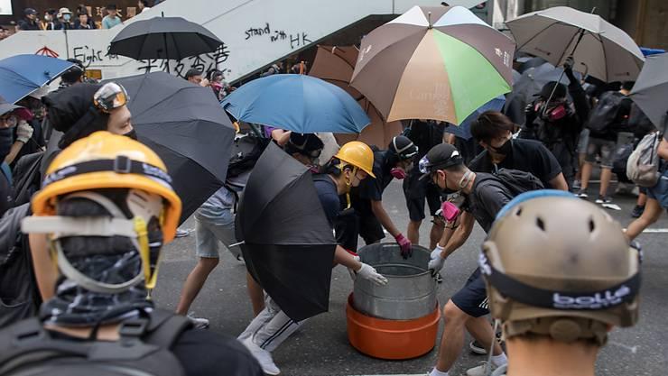 Protestierende in Hongkong haben am Sonntag zahlreiche Barrikaden aus Abfallbehältern errichtet.