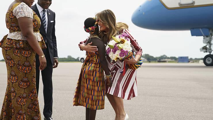 US-First Lady Melania Trump umarmt auf dem Flughafen von Accra ein Blumenmädchen vor dem Protokollchef des ghanaischen Präsidenten.