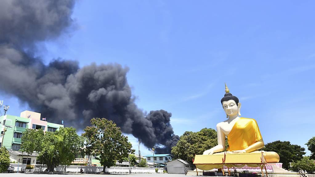 Rauch steigt hinter einer riesigen Buddha-Statue in der Provinz Samut Prakan auf. In Thailand ist es in einer Chemiefabrik zu einer schweren Explosion gekommen. Foto: Uncredited/AP/dpa
