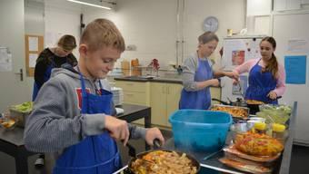 Schüler Kilian Schlienger (13) kocht zusammen mit Mitschülerinnen und der Hauswirtschaftslehrerin Fajitas für die ganze Schule und die Gäste.