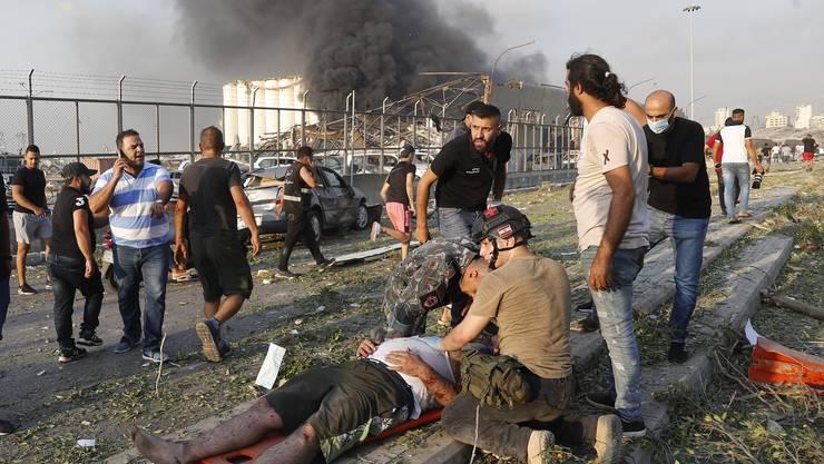 Chaos nach der Explosion: Rettungskräfte kümmern sich um einen Verletzten.