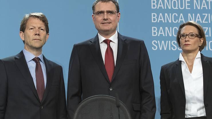 Das dreiköpfige Nationalbank-Direktorium um Präsident Thomas Jordan (Mitte), Vizepräsident Fritz Zurbrügg und Andrea Maechler verfolgt seinen geldpolitischen Kurs unverändert weiter. (Archiv)