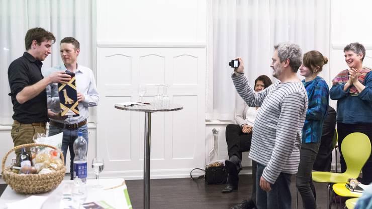 Parteipräsident Daniel Hölzle (links) würdigt Jonas Fricker. Von den Parteikollegen gibt es Standing Ovations.