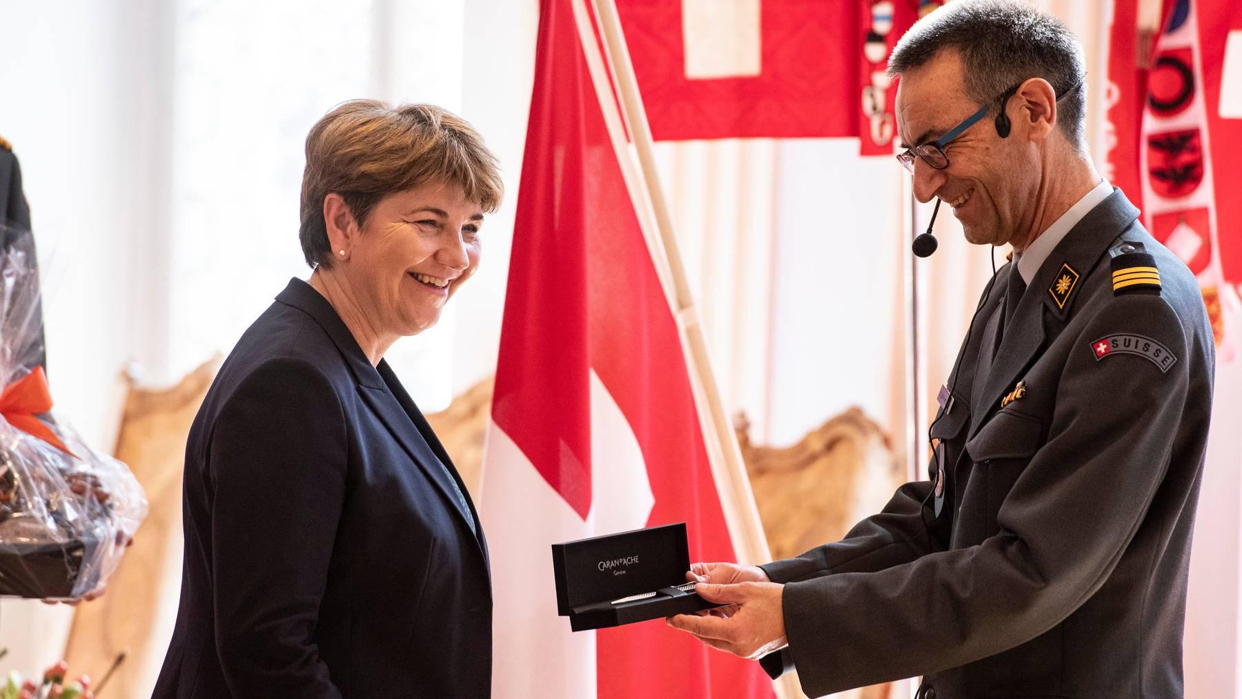 Stefan Holenstein, Präsident der Offiziersgesellschaft, schenkt Verteidigungsministerin Viola Amherd einen Kugelschreiber.