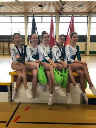 Maura (l.) erkämpft sich den dritten Rang auf dem AG Podest und präsentiert sich zusammen mit den P3 Turnerinnen Shannon, Madleina, Jasmin und Ileya.