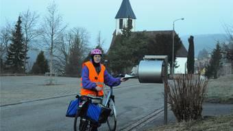 Ausgerüstet mit Leuchtweste, Velohelm und Velotasche, beliefertCilli Schär frühmorgens alle Briefkästen in Bözen mit Zeitungen. tab