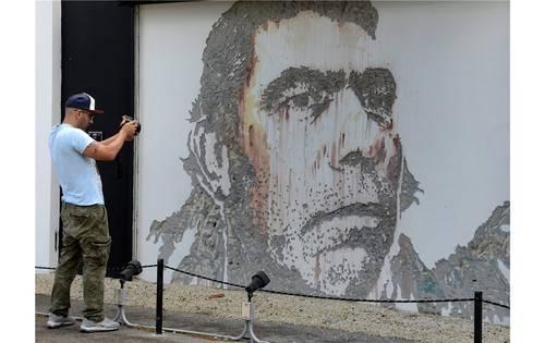 Ein Graffiti-Künstler schlägt sein Bild direkt in den Putz einer Hauswand.