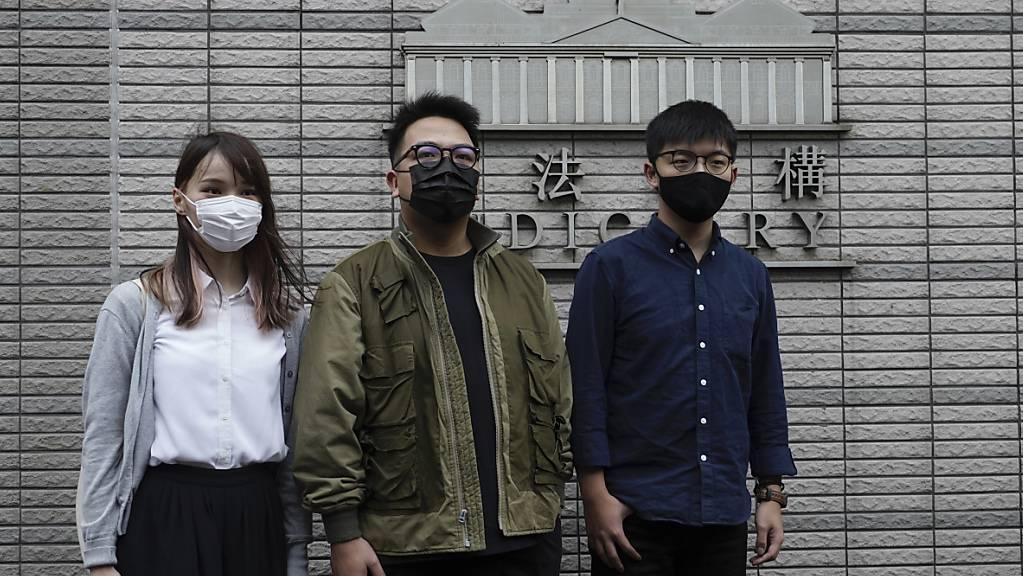Die Pro-Demokratie-Aktivisten Wong, Chow und Lam stehen vor Gericht wegen der Belagerung einer Polizeistation während der Anti-Regierungs-Proteste im vergangenen Jahr.