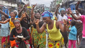 Menschen im Armenviertel Monrovias feiern das Ende der Quarantäne
