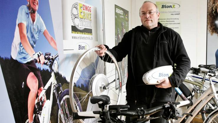 Christian Zingg mit Hinterrad mit Nabenmotor und Akku: Aus dem Velo wird ein Berggänger.  Peter Siegrist