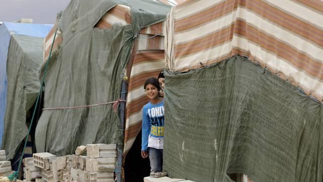 Ein Mädchen schaut zwischen zwei Zelten eines Flüchtlingslagers im Libanon nahe der syrischen Grenze hervor (Archiv)