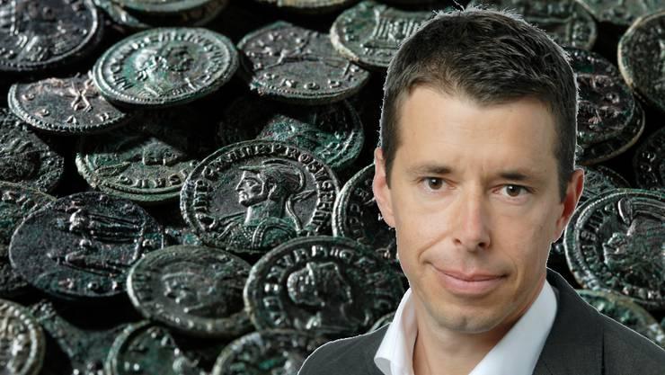 Dr. Georg Matter, Kantonsarchäologe Kanton Aargau. Im Hintergrund: Der über viertausend Münzen grosse Schatz.