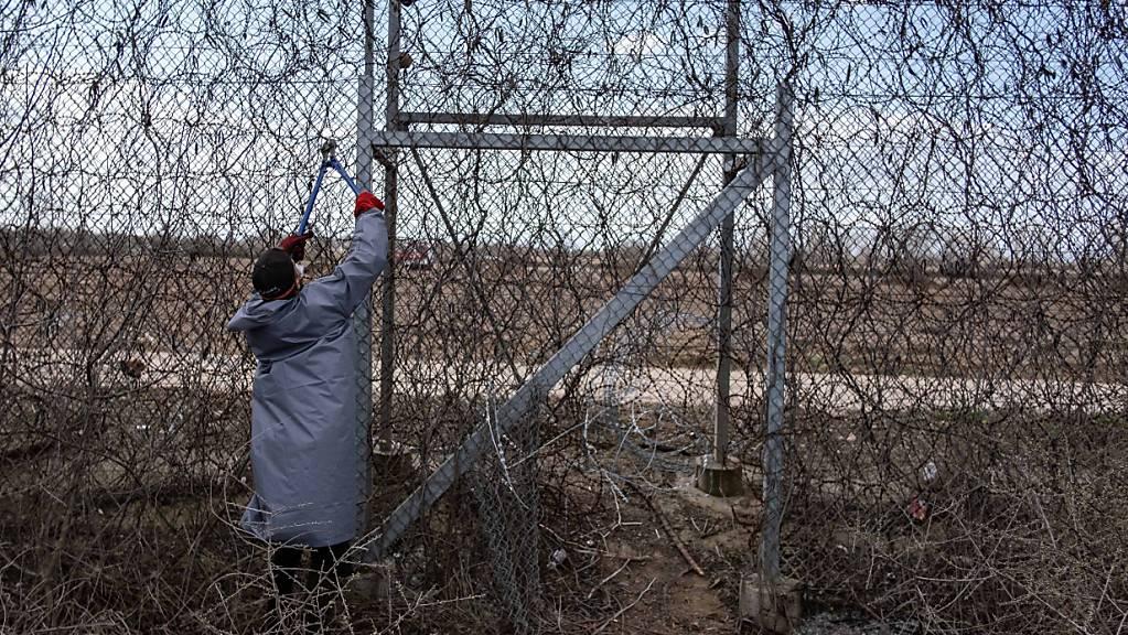 Ein Migrant steht am Grenzzaun an der türkisch-griechischen Grenze und versucht, mit einer Drahtschere den Zaun durchzuschneiden.