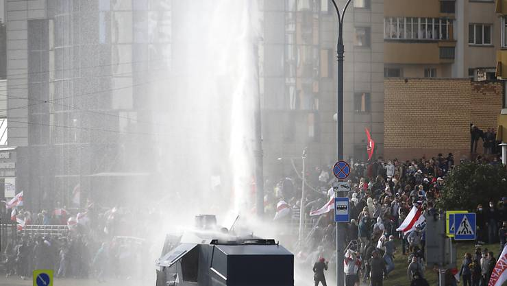 Polizisten setzten einen Wasserwerfer gegen Demonstranten ein. Trotz eines Großaufgebots an Sicherheitskräften haben Zehntausende Menschen gegen den autoritären Staatschef Lukaschenko demonstriert. Foto: Uncredited/AP/dpa