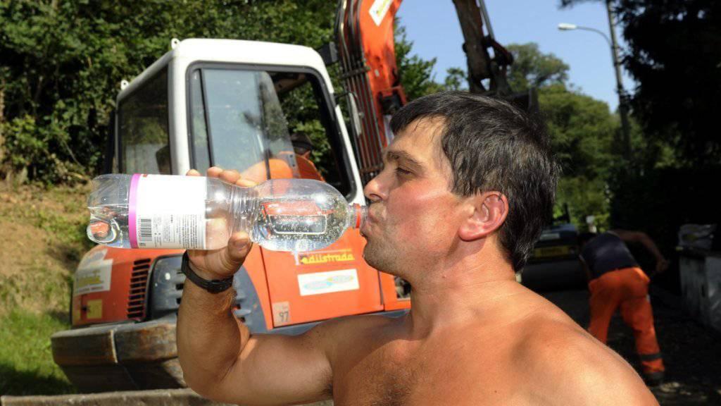 Strassenarbeiter sind bei Belagsarbeiten meist der prallen Sonne ausgesetzt. Viel trinken ist für sie ein Muss. Die Gewerkschaft Unia mahnt die Arbeitgeber vor der Hitzewelle an ihre Sorgfaltspflicht. Ab 35 Grad müssten Baustellen geschlossen werden. (Archivbild)