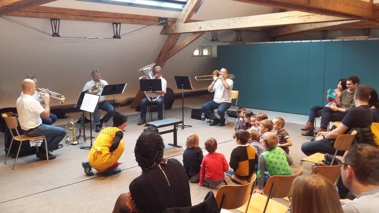 Clown Flupp und die jungen Konzertbesucherinnen und -besucher lauschen gespannt den Klängen des Blechbläserensembles Quintessenz.