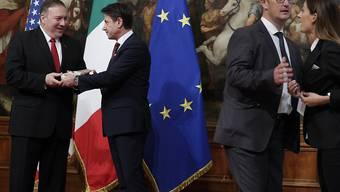 Sorge um den Export von Wein, Käse und anderem mehr: US-Aussenminister Mike Pompeo (links) hat von einer Journalistin gerade ein Paket Parmesan erhalten. Die Journalistin (rechts) wird weggeführt.
