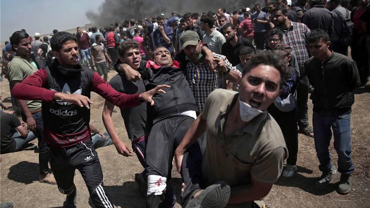 Demonstranten tragen einen Verletzten aus der Gefahrenzone:Im Gazastreifen eskalierte die Gewalt zwischen Palästinensern und israelischem Militär. Keystone