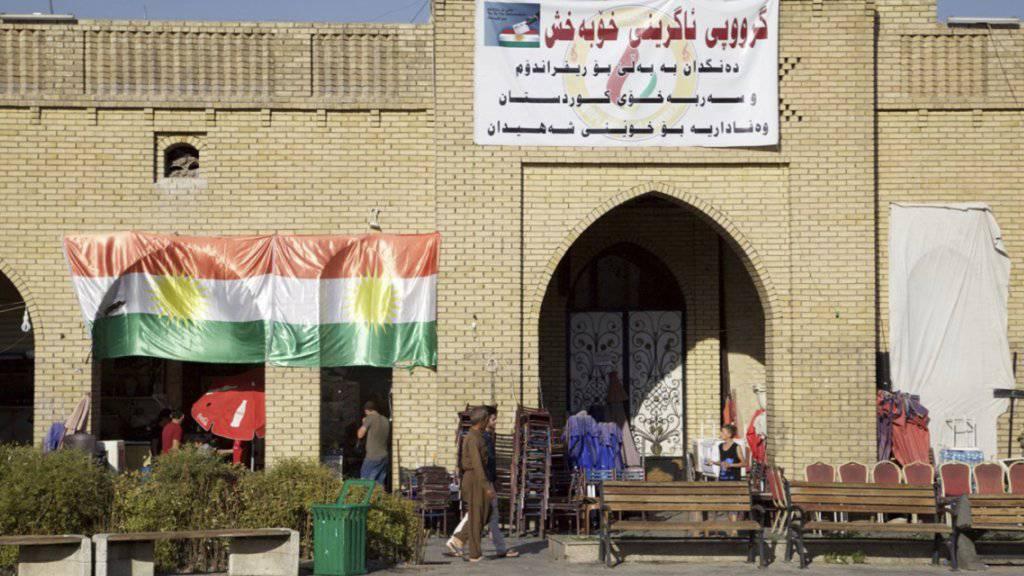 Eine kurdische Flagge und ein Abstimmungsplakat, das zu einem Ja beim Unabhängigkeitsreferendum in der autonomen Kurdenregion im Nordirak aufruft.