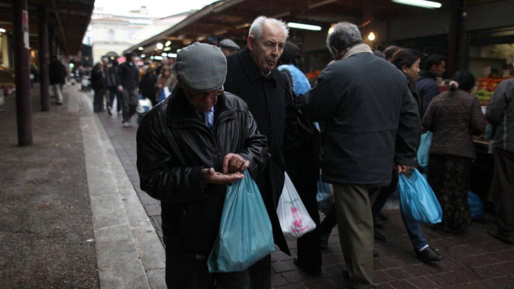 Ein älterer Mann zählt auf dem zentralen Athener Gemüsemarkt nach einem Einkauf seine Euro-Münzen. Laut einer Studie lebt jeder zweite Grieche aufgrund der Krise des Landes unter Angstzuständen, innerer Unruhe und Unsicherheit (Archiv)