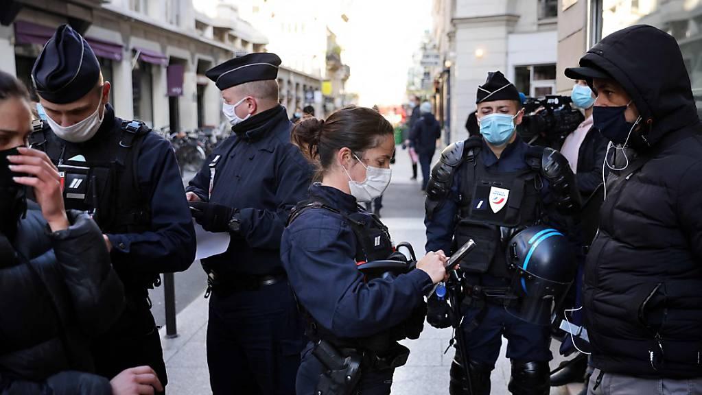 Polizisten kontrollieren Ausweise von Passanten in Paris.