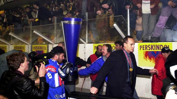 Playoffserien zwischen Zürich und Lugano sind immer eine emotionale Sache. Hier müsssen Larry Huras und seine Spieler mit dem Meisterpokal vor wütenden Lugano-Fans flüchten.