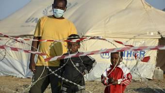 Ein Migrant steht mit zwei Kindern vor einem Stacheldrahtzaun im neu errichteten temporären Flüchtlingslager in Kara Tepe. Foto: Panagiotis Balaskas/AP/dpa