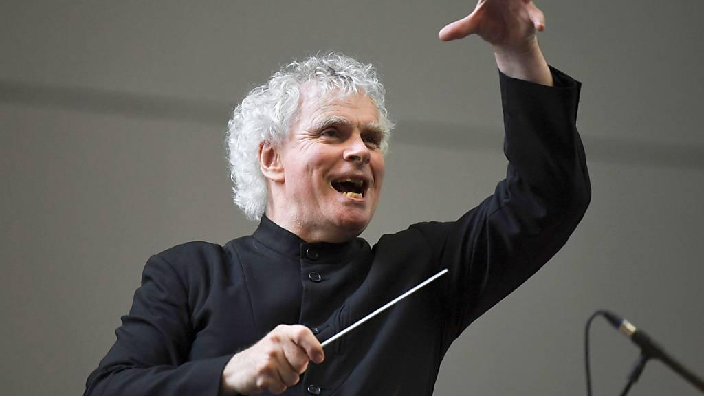 ARCHIV - Sir Simon Rattle, ehemaliger Chefdirigent der Berliner Philharmoniker, dirigiert das London Symphony Orchestra in der Turbinenhalle des Tate Modern Museums. Foto: Doug Peters/PA/AP/dpa
