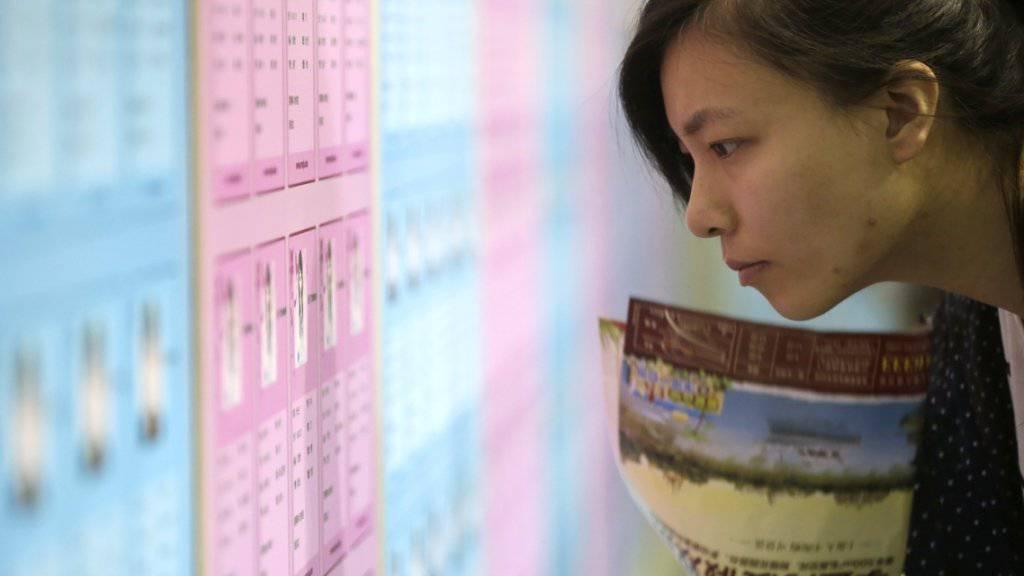 Eine junge Chinesin blickt auf den Aushang einer Partnerbörse: Der «Tag der Singles» wurde in den Neunziger Jahren von Studenten als Antwort auf den Valentinstag ins Leben gerufen (Archiv).