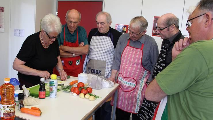 Céline Schor zeigt den Männern, wie man Zwiebeln fein schneidet. bie