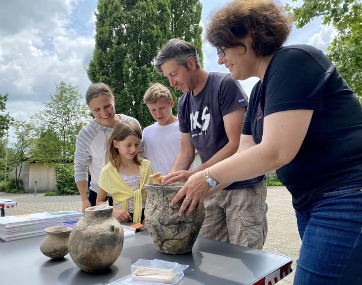 Archäologinnen und Archäologen vom Amt für Archäologie zeigen originale Pfahlbaufunde.