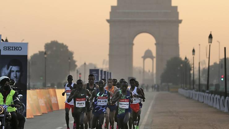 Teilnehmer des Halbmarathons vor dem «India Gate» in Neu Delhi. Foto: Altaf Qadri/AP/dpa