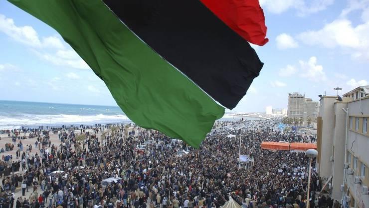 Aufständische haben die Flagge des alten Königreichs Libyen gehisst. Sie war die offizielle Flagge Libyens nach der Unabhängigkeit 1951 unter König Idris bis zur Revolution unter Muammar Gaddafi 1969.