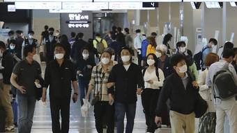 Menschen mit Mundschutz gehen am Flughafen Gimpo durch die Gänge des Inlandsterminals. Die Behörden haben alle Flugzeugpassagiere auf Grund der Corona-Pandemie zum Tragen von Gesichtsmasken aufgefordert. Foto: Ahn Young-Joon/AP/dpa