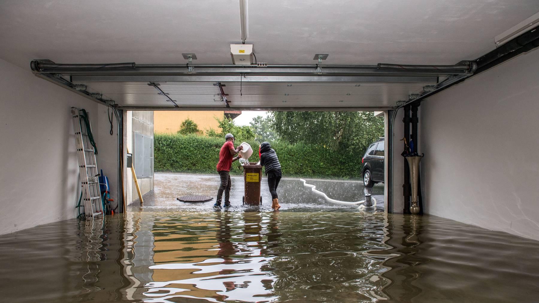 Das Unwetter hat diverse Keller und Garagen überflutet: Gaby Blätter mit ihrem Schwiegersohn am Wasser schöpfen im Neuhof Quartier in Emmenbrücke.
