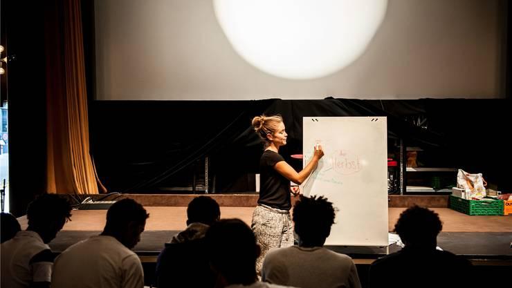 Flüchtlinge besuchen im «Kafi Royal» einen Deutschkurs: Lea Stirnimann, freiwillige Lehrerin, nutzt neben Worten auch Zeichnungen zur Überwindung der Sprachbarrieren.