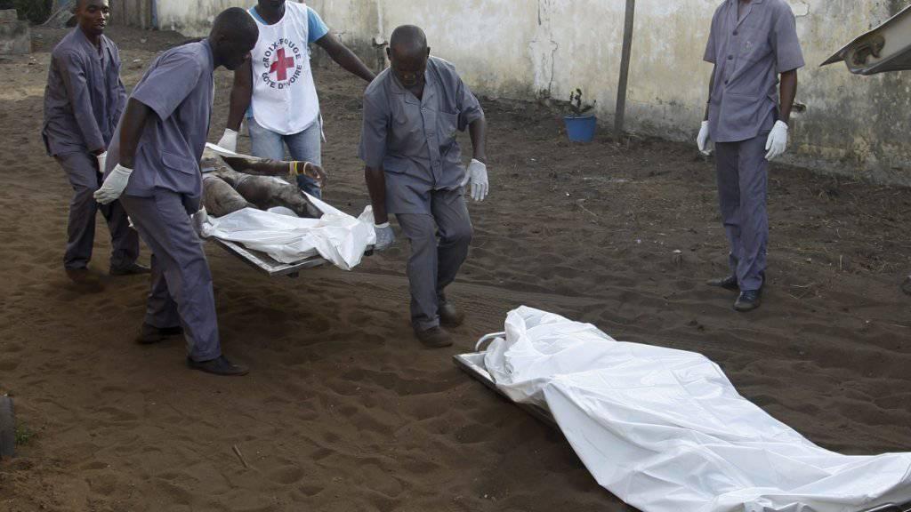Polizisten und Helfer in der Elfenbeinküste tragen Opfer der Anschläge von Grand-Bassam weg.