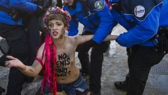 Polizisten in Davos führen eine Femen-Aktivistin ab