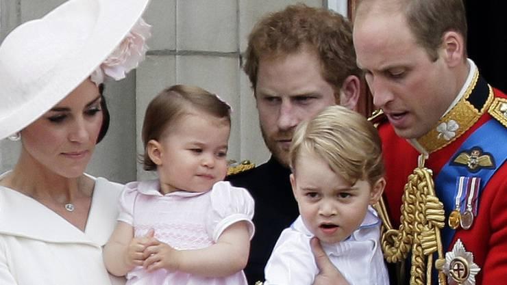 Sitzen bald im Flugzeug nach Kanada: Prinz William und seine Frau Kate mit den Kindern Charlotte und George. Im Hintergrund steht Prinz Harry. (Archivbild)