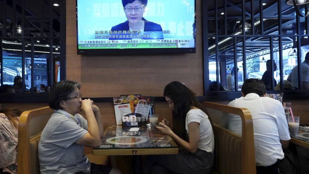 Das Fernsehen überträgt die Verkündung des Vermummungsverbot für Demonstranten durch die Hongkonger Regierungschefin Carrie Lam.