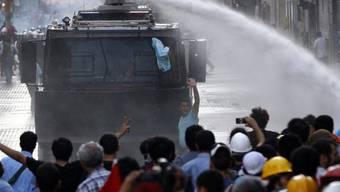 Die Polizei drängt Demonstranten mit Wasserwerfern zurück
