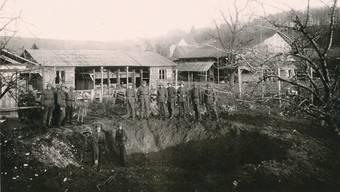 Die Schweizer Soldaten posieren in Koblenz für ein Gruppenfoto. Im Hintergrund die Mannschaftsbaracke, die durch die Druckwelle einer Bombe beschädigt wurde.